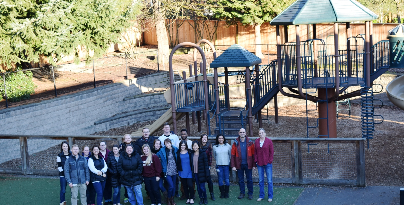 Specialty School staff pose on playground
