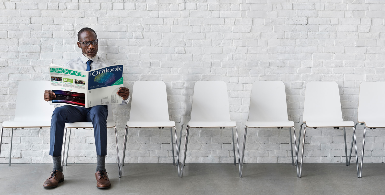 Man reading issue of healthy outlook sitting on white chair