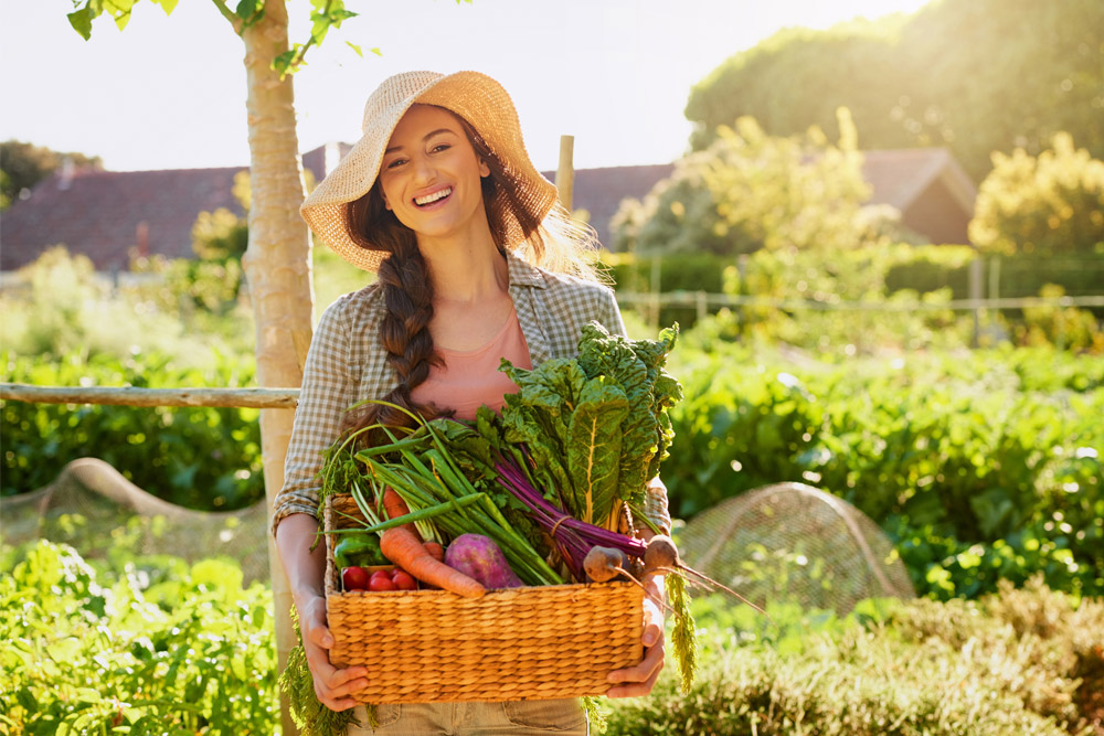 woman outside holding box of veggies and fruit