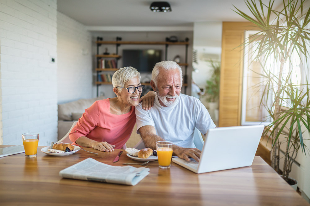 mature couple using laptop at table