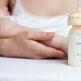 A bottle of breast milk and an adult holding a sleeping child.
