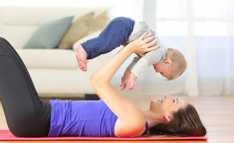 Mother holding baby on yoga mat